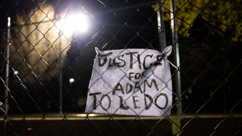 """BROOKLYN CENTER, MN - APRIL 17: A piece of cloth with a note reading """"Justice for Adam Toledo"""" is affixed to fencing outside the Brooklyn Center police station on April 17, 2021 in Brooklyn Center, Minnesota. This is the seventh day of protests in the suburban Minneapolis city following the fatal shooting of 20-year-old Daunte Wright by Brooklyn Center police officer Kimberly Potter, who has since resigned from the force and today was charged with second-degree manslaughter. (Photo by Stephen Maturen/Getty Images)"""