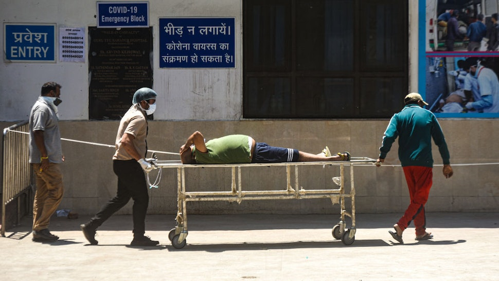 NEW DELHI, INDIA APRIL 24: Relatives carry a Covid-19 patient on a stretcher as they leave from GTB Hospital , on April 24, 2021 in New Delhi, India. (Photo by Amal KS/Hindustan Times via Getty Images)