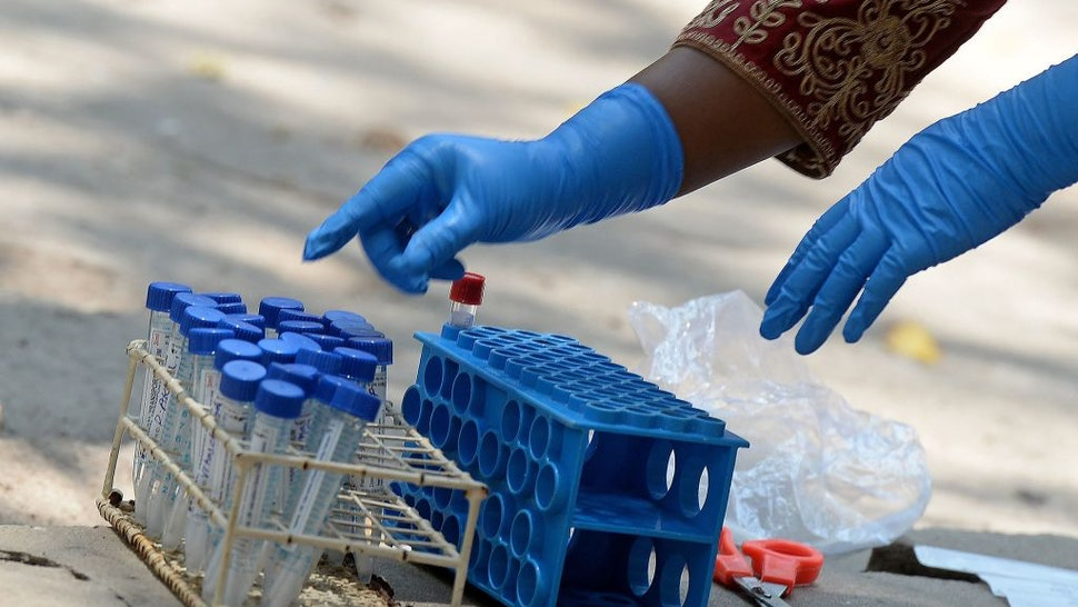 A medical worker arranges swab samples from the Reverse Transcription Polymerase Chain Reaction (RT-PCR) tests conducted for the Covid-19 coronavirus screening at a testing centre in Hyderabad on April 29, 2021. (Photo by NOAH SEELAM / AFP) (Photo by NOAH SEELAM/AFP via Getty Images)