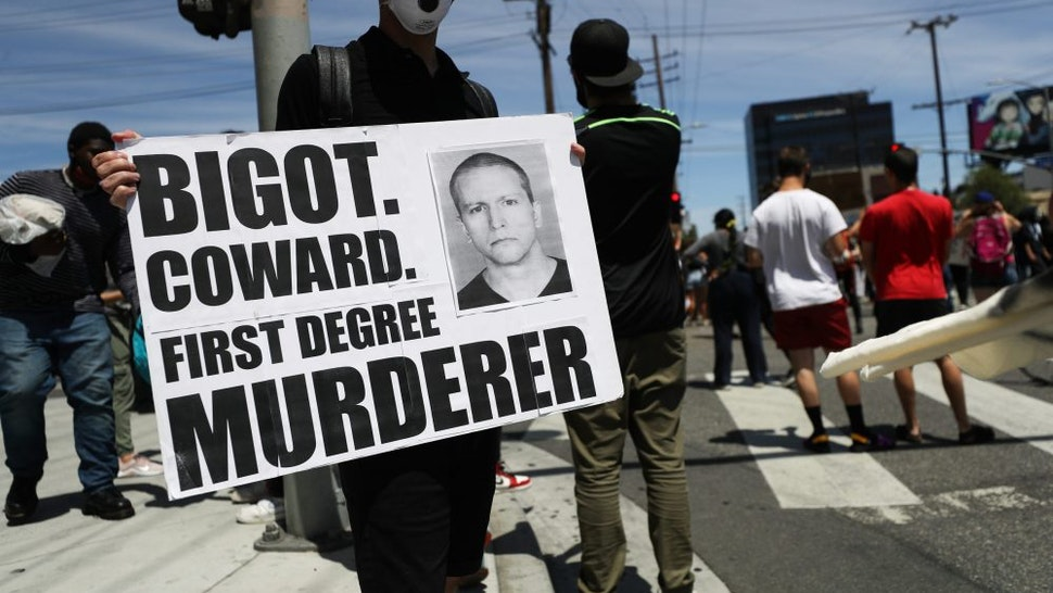 LOS ANGELES, CALIFORNIA - MAY 30: A protester holds a sign with a photo of former Minneapolis police officer Derek Chauvin during demonstrations following the death of George Floyd on May 30, 2020 in Los Angeles, California. Chauvin was taken into custody for Floyd's death. Chauvin has been accused of kneeling on Floyd's neck as he pleaded with him about not being able to breathe. Floyd was pronounced dead a short while later. Chauvin and 3 other officers, who were involved in the arrest, were fired from the police department after a video of the arrest was circulated.