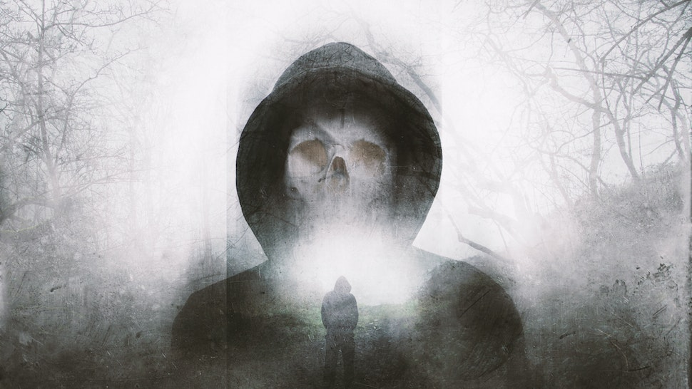 A double exposure of a scary hooded figure with a skull for a face. Over layered with a forest in winter. with a blurred, grunge, abstract edit - stock photo