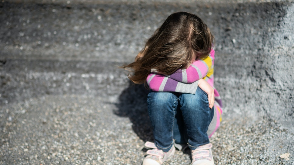 Isolated kid hiding her face from camera - stock photo
