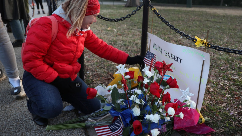 Melody Black, from Minnesota, becomes emotional as she visits a memorial setup near the U.S. Capitol Building for Ashli Babbitt who was killed in the building after a pro-Trump mob broke in on January 07, 2021 in Washington, DC.