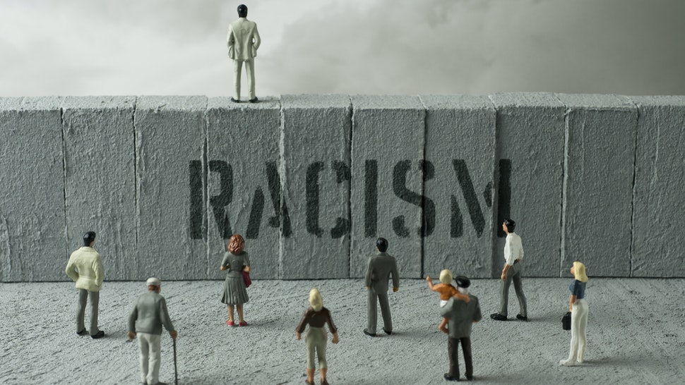 People figurines looking at the Racism warning on the wall. Uncertainty concept