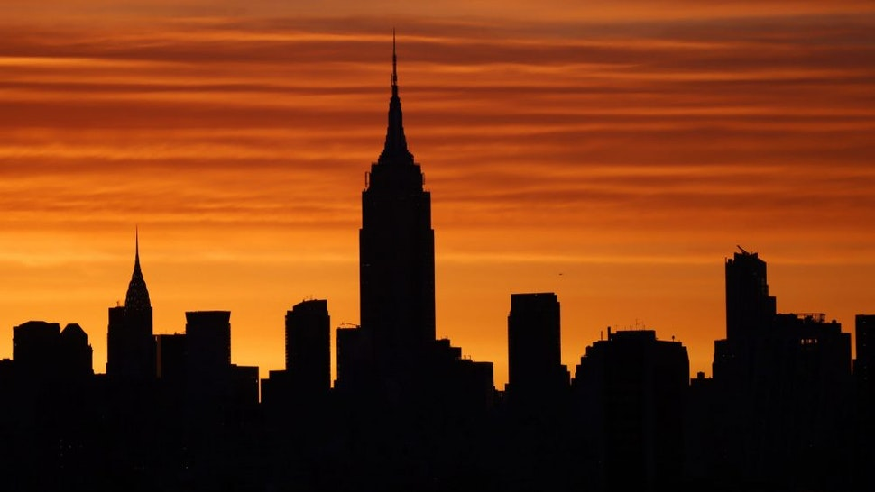 JERSEY CITY, NJ - APRIL 7: The sun rises behind the Empire State Building and Chrysler Building in New York City on April 7, 2021 as seen from Jersey City, New Jersey.