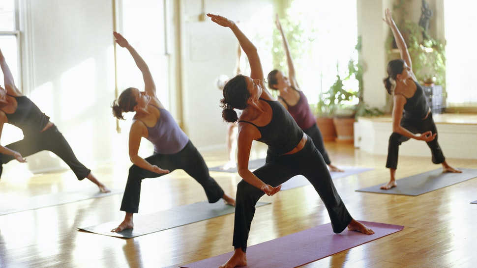 Group of women stretching in yoga class, arms raised - stock photo
