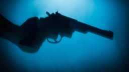 Silhouette of man's hand holding a pistol