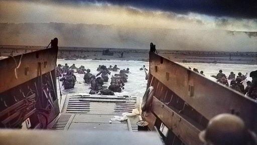 """Digitally colorized image of """"Into the Jaws of Death"""", a photograph by Robert F Sargent of the United States Army First Infantry Division disembarking from an LCVP (landing craft) onto Omaha Beach during the Normandy Landings on D Day during World War 2, June 6, 1944. (Photo via Smith Collection/Gado/Getty Images)."""