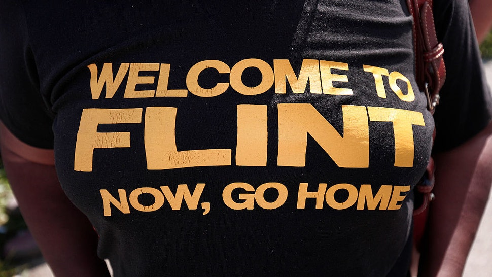 FLINT, MI - SEPTEMBER 14: An anti-Trump protestor wears a shirt that expresses her opinion while waiting for Republican presidential nominee Donald Trump to arrive for a visit to the Flint Water Treatment Plant September 14, 2016 in Flint, Michigan. While in Flint, Trump will also meet with several ministers from the area.