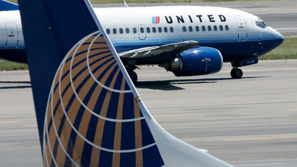 WASHINGTON - AUGUST 16: A United Airlines aircraft passes by a Continental Airlines aircraft as it taxis to takeoff from the runway of Ronald Reagan National Airport August 16, 2006 in Washington, DC.