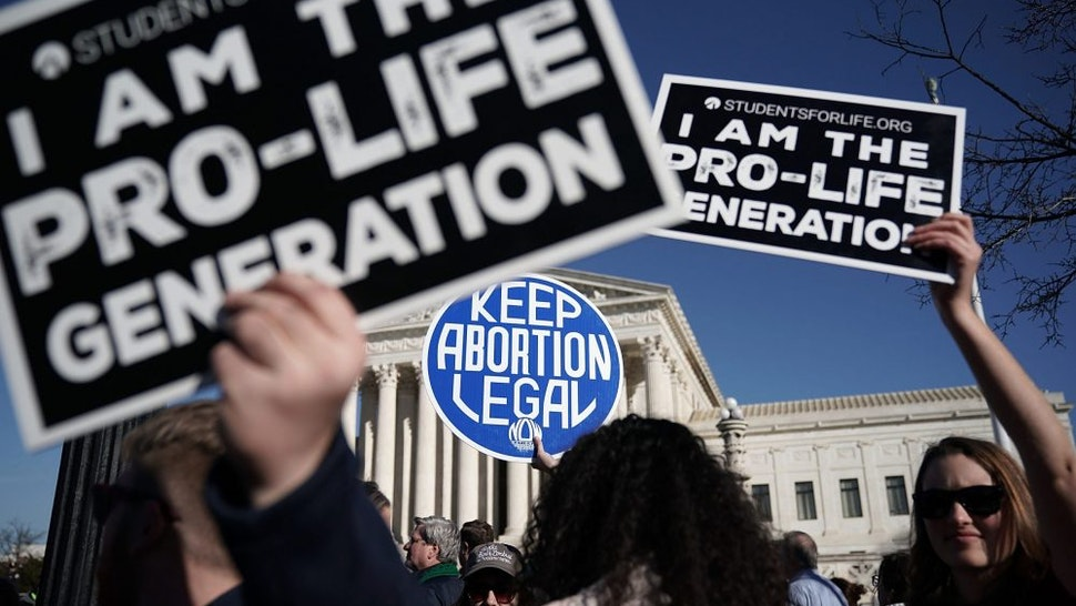 WASHINGTON, DC - JANUARY 19: Pro-life activists try to block the sign of a pro-choice activist during the 2018 March for Life January 19, 2018 in Washington, DC. Activists gathered in the nation's capital for the annual event to protest the anniversary of the Supreme Court Roe v. Wade ruling that legalized abortion in 1973.