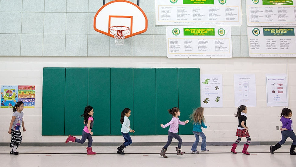 STERLING, VA - FEB6: Kindergarten students at Guilford Elementary school run during P.E. class, February 6, 2015. The school system in Loudoun County, one of the wealthiest counties in the US by some measures, only provides full-day kindergarten at Title I schools like Guilford, which receive special federal funding because of high rates of poverty. Because Guilford is full-day, it's able to offer its five-year-olds things like PE, arts, music and more lessons on core subjects like math and reading.