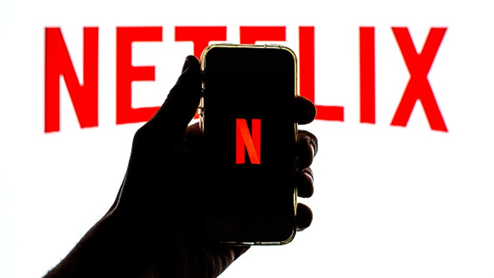 SPAIN - 2021/03/23: In this photo illustration the Netflix App seen displayed on a smartphone screen with the Netflix logo in the background.