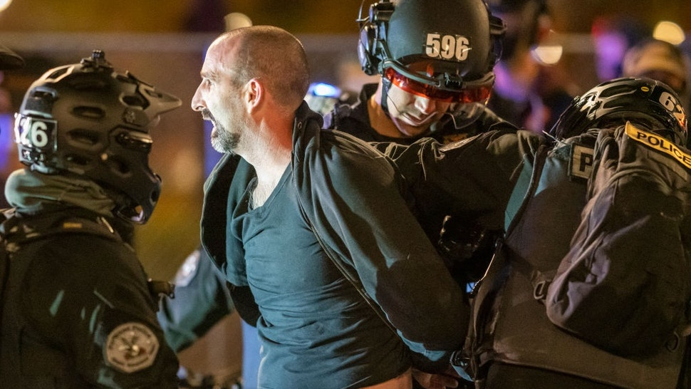 PORTLAND, OR - APRIL 16: Portland Police arrest a protester following riot declaration on April 16, 2021 in Portland, Oregon.