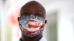 "DOUGLASVILLE, GEORGIA - OCTOBER 28: U.S. Sen. Tim Scott (R-SC) wears a face mask that reads ""God Bless America"" during a campaign event with U.S. Sen. Kelly Loeffler (R-GA) at Metro Garage Door on October 28, 2020 in Douglasville, Georgia. Sen. Loeffler is running for re-election after being appointed by Georgia Governor Brian Kemp in January following the retirement of Sen. Johnny Isakson (R-GA)."