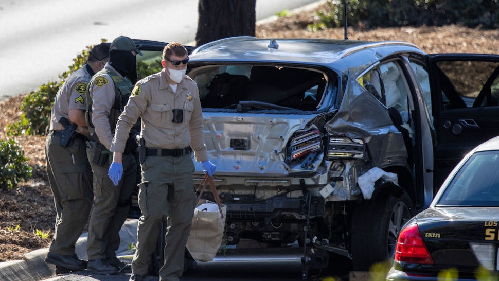 ROLLING HILLS ESTATES, CA - FEBRUARY 23: Los Angeles County Sheriff deputies gather evidence from the car that golf legend Tiger Woods was driving when seriously injured in a rollover accident on February 23, 2021 in Rolling Hills Estates, California. Rescuers used hydraulic rescue tools to extricate him from the car where he reportedly sustained major leg injuries. Law enforcement reports that there was no evidence of impairment. He was in town to participate in The Genesis Invitational golf tournament.