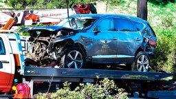 """A tow truck recovers the vehicle driven by golfer Tiger Woods in Rancho Palos Verdes, California, on February 23, 2021, after a rollover accident. - Woods was hospitalized Tuesday after a car crash in which his vehicle sustained """"major damage,"""" the Los Angeles County Sheriff's department said. Woods, the sole occupant, was removed from the wreckage by firefighters and paramedics, and suffered """"multiple leg injuries,"""" his agent said in a statement to US media."""