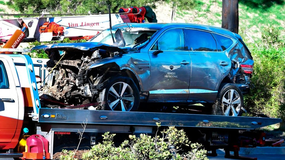 "A tow truck recovers the vehicle driven by golfer Tiger Woods in Rancho Palos Verdes, California, on February 23, 2021, after a rollover accident. - Woods was hospitalized Tuesday after a car crash in which his vehicle sustained ""major damage,"" the Los Angeles County Sheriff's department said. Woods, the sole occupant, was removed from the wreckage by firefighters and paramedics, and suffered ""multiple leg injuries,"" his agent said in a statement to US media."