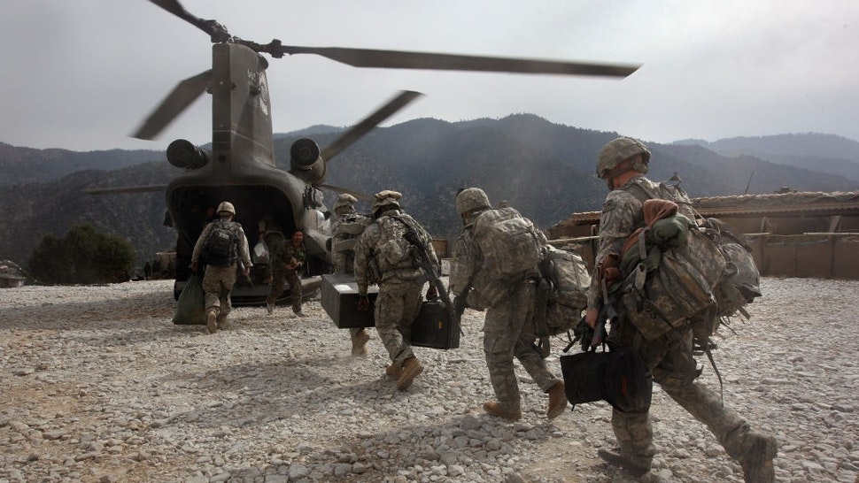 KORENGAL VALLEY, AFGHANISTAN - OCTOBER 27: U.S. soldiers board an Army Chinook transport helicopter after it brought fresh soldiers and supplies to the Korengal Outpost on October 27, 2008 in the Korengal Valley, Afghanistan. The military spends huge effort and money to fly in supplies to soldiers of the 1-26 Infantry based in the Korengal Valley, site of some of the fiercest fighting of the Afghan war. The unpaved road into the remote area is bad and will become more treacherous with the onset of winter. (Photo by
