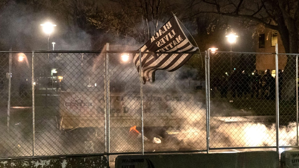 A Black Lives Matter flag is seen after curfew as demonstrators protest the death of Daunte Wright who was shot and killed by a police officer in Brooklyn Center, Minnesota on April 12, 2021. - A suburb of Minneapolis was under curfew early April 12, 2021 after US police fatally shot a young Black man, sparking protests not far from where a former police officer was on trial for the murder of George Floyd.Hundreds of people gathered outside the police station in Brooklyn Center, northwest of Minneapolis, with police later firing teargas and flash bangs to disperse the crowd, according to an AFP videojournalist.
