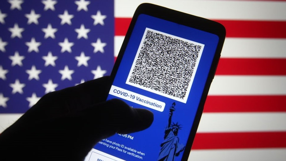 UKRAINE - 2021/03/28: In this photo illustration, Excelsior Pass app which provides digital proof of COVID-19 vaccination or negative test results seen displayed on a smartphone screen in front of the US flag. The first COVID-19 vaccine passports' in the US called the Excelsior Pass was launched on Friday in New York, reportedly by the media on 27 March. Excelsior Pass provides digital proof of COVID-19 vaccination or negative test results of three types of passes: COVID-19 Vaccination Pass, COVID-19 PCR Test Pass, and COVID-19 Antigen Test Pass. (Photo Illustration by