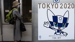 """TOPSHOT - A passenger wearing a face mask stands next to a poster of Tokyo 2020 Olympic mascot Miraitowa on a train in Tokyo on April 20, 2020. - A Japanese expert who has criticised the country's response to the coronavirus warned on April 20 that he is """"pessimistic"""" that the postponed Olympics can be held even in 2021. (Photo by Philip FONG / AFP) (Photo by"""