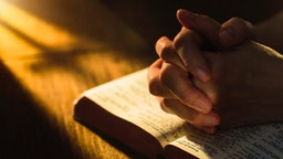 Close up of hands clasped on open Bible - stock photo.