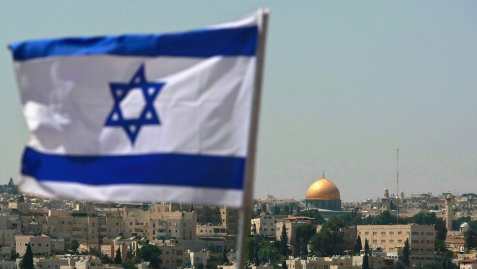 An Israeli flag flies from the Kidmat Zion Jewish settlement community on the outskirts of the Arab village of Abu Dis, where the Old City with its golden Dome of the Rock Islamic shrine is seen in the background, August 18, 2008 in East Jerusalem, Israel.