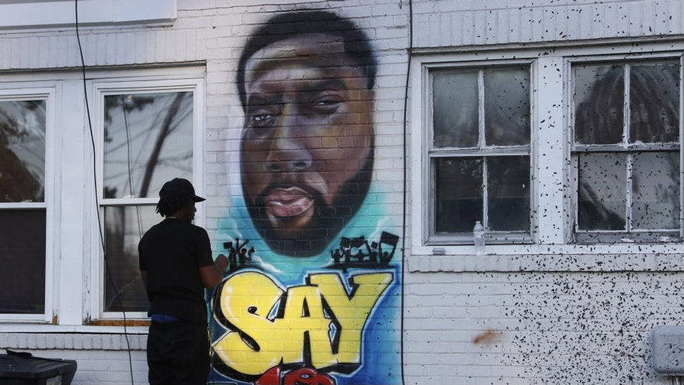ELIZABETH CITY, NORTH CAROLINA - MAY 01: Ulysses Edwards paints a portrait of Andrew Brown Jr. on the side of the house in the area where he was killed on May 01, 2021 in Elizabeth City, North Carolina. Mr. Brown was shot to death by Pasquotank County Sheriff's deputies. (Photo by Joe Raedle/Getty Images)