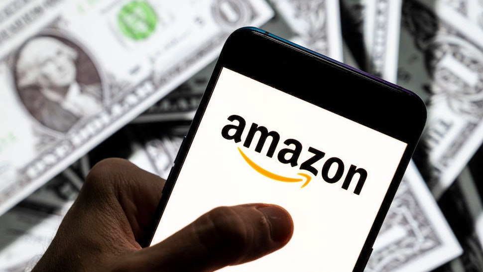 CHINA - 2021/04/23: In this photo illustration the American electronic commerce and cloud computing company Amazon logo seen on an Android mobile device screen with the currency of the United States dollar icon, $ icon symbol in the background. (Photo Illustration by Budrul Chukrut/SOPA Images/LightRocket via Getty Images)