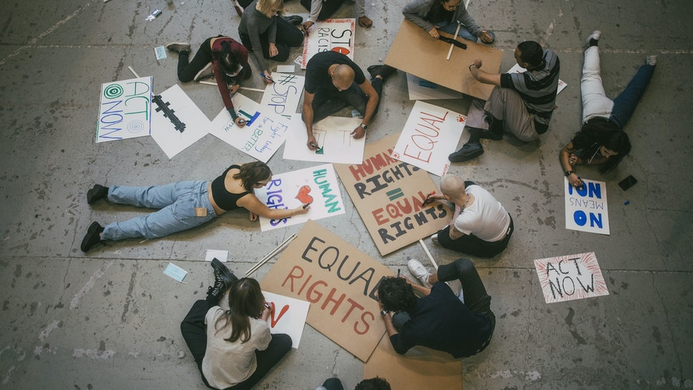 Directly above of male and female protestor preparing posters for social movement