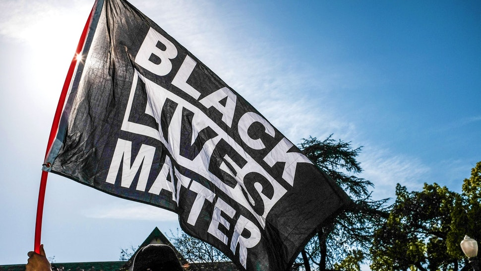 LOS ANGELES, CALIFORNIA, UNITED STATES - 2021/04/20: A protester waves a Black Lives Matter flag during the demonstration. Hours after the verdict of the Derek Chauvin trial, protesters meet outside of Los Angeles Mayor Eric Garcetti's home to protest his proposed funding of the Los Angeles Police Department.