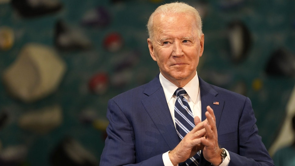 """U.S. President Joe Biden applauds while Ralph Northam, governor of Virginia, not pictured, speaks at Sportrock Climbing Center during an event in Alexandria, Virginia, U.S., on Friday, May 28, 2021. Biden this week said he ordered the U.S. intelligence community to """"redouble"""" its effort to determine where the coronavirus came from, after conflicting conclusions about whether its origins are natural or a lab accident."""