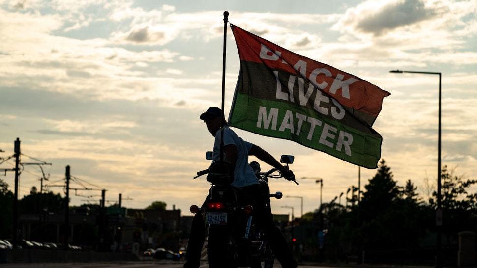 ST. PAUL, MN - MAY 24: A man on a motorcycle displays a Black Lives Matter flag during a march and rally at the Minnesota State Capitol on Monday, May 24, 2021 in St. Paul, MN.