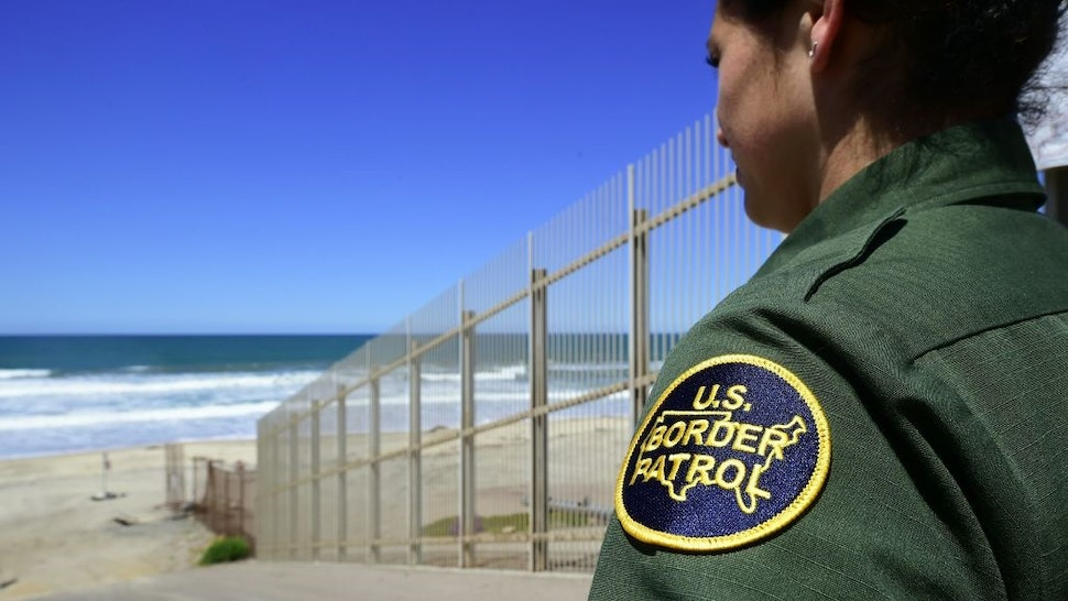 A US Customs and Border Protection agent looks toward the ocean from within the Border Infrastructure System, a no man's land area between the wall and fence which runs for 14 miles inland from the Pacific Ocean separating California from Mexico on April 17, 2018 in San Diego, California across from La Playa, Mexico a day after California rejected plans by the federal government for National Guard troops on the border.