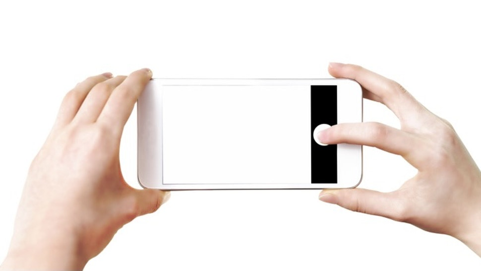 Making photos on smartphone - stock photo Mock-up of making photo on a smartphone - woman's hands holding mobile phone and touching screen isolated on white background WDnet via Getty Images