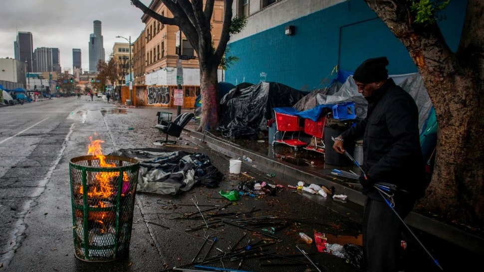 A homeless man makes a fire from trash to keep warm in Skidrow on Thanksgiving day in Los Angeles, California, November 28, 2019.