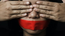Asian woman blindfold wrapping mouth with red adhesive tape on black background. Freedom speech censorship and stop talk, International Human Right day (Asian woman blindfold wrapping mouth with red adhesive tape on black background. Freedom speech ce