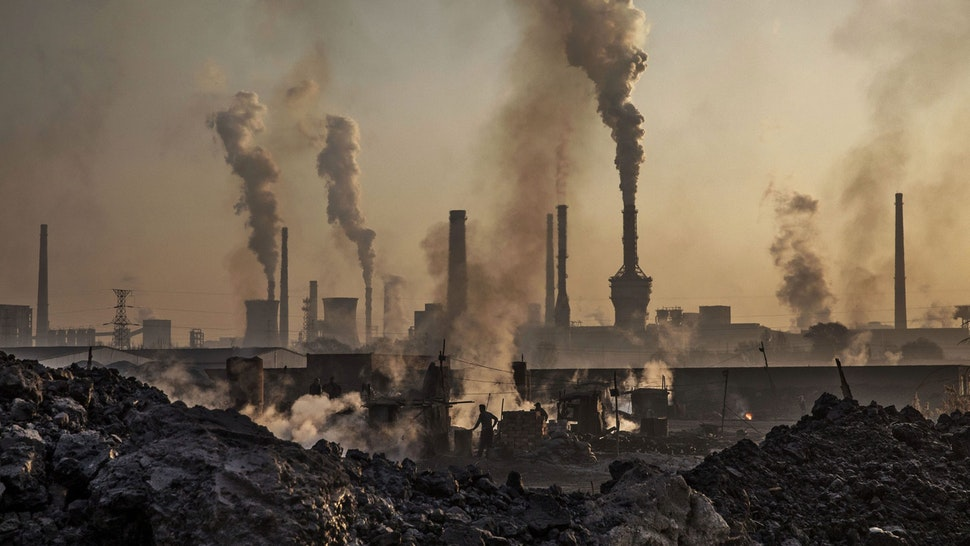 """INNER MONGOLIA, CHINA - NOVEMBER 04: Smoke billows from a large steel plant as a Chinese labourer works at an unauthorized steel factory, foreground, on November 4, 2016 in Inner Mongolia, China. To meet China's targets to slash emissions of carbon dioxide, authorities are pushing to shut down privately owned steel, coal, and other high-polluting factories scattered across rural areas. In many cases, factory owners say they pay informal 'fines' to local inspectors and then re-open. The enforcement comes as the future of U.S. support for the 2015 Paris Agreement is in question, leaving China poised as an unlikely leader in the international effort against climate change. U.S. president-elect Donald Trump has sent mixed signals about whether he will withdraw the U.S. from commitments to curb greenhouse gases that, according to scientists, are causing the earth's temperature to rise. Trump once declared that the concept of global warming was """"created"""" by China in order to hurt U.S. manufacturing. China's leadership has stated that any change in U.S. climate policy will not affect its commitment to implement the climate action plan. While the world's biggest polluter, China is also a global leader in establishing renewable energy sources such as wind and solar power."""