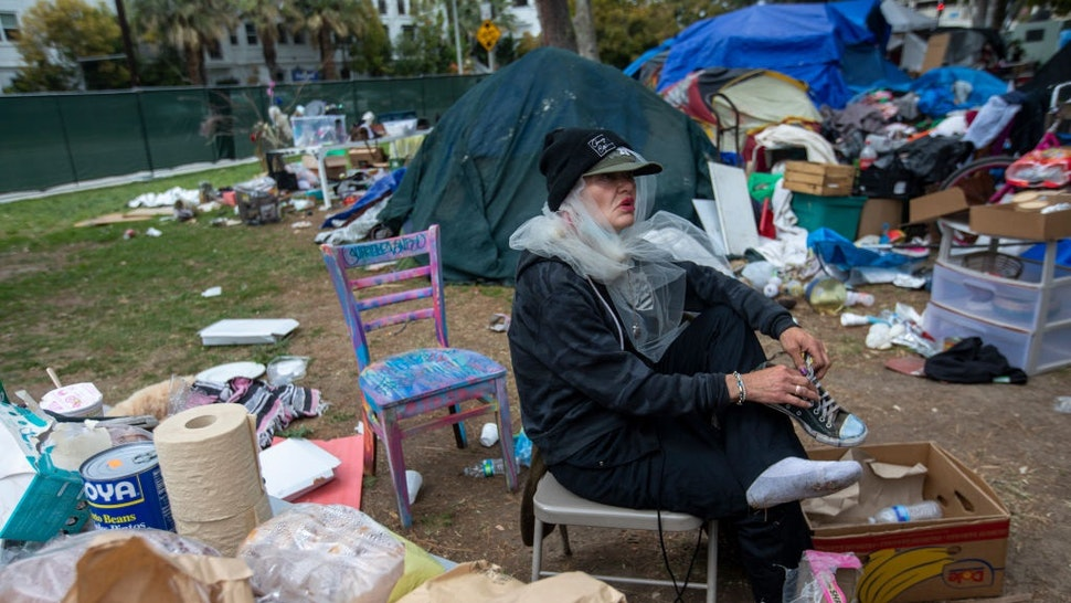 LOS ANGELES, CA - MARCH 25: Still wearing her wedding vail Valerie Zeller puts on her shoes as she is packing outside her tent next other tents at Echo Park Lake Thursday, March 25, 2021 in Los Angeles, CA.