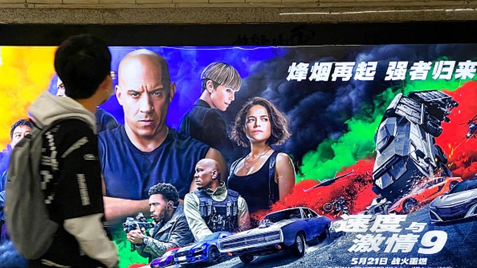 BEIJING, CHINA - MAY 04: A man walks by a poster for film 'Fast & Furious 9' at a shopping centre on the fourth day of the May Day holiday on May 4, 2021 in Beijing, China