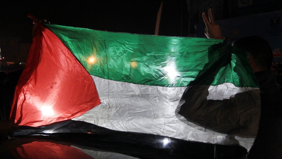 Palestinians hold up their national flag as they celebrate the beginning of the truce with Israel in Gaza City on November 21, 2012.