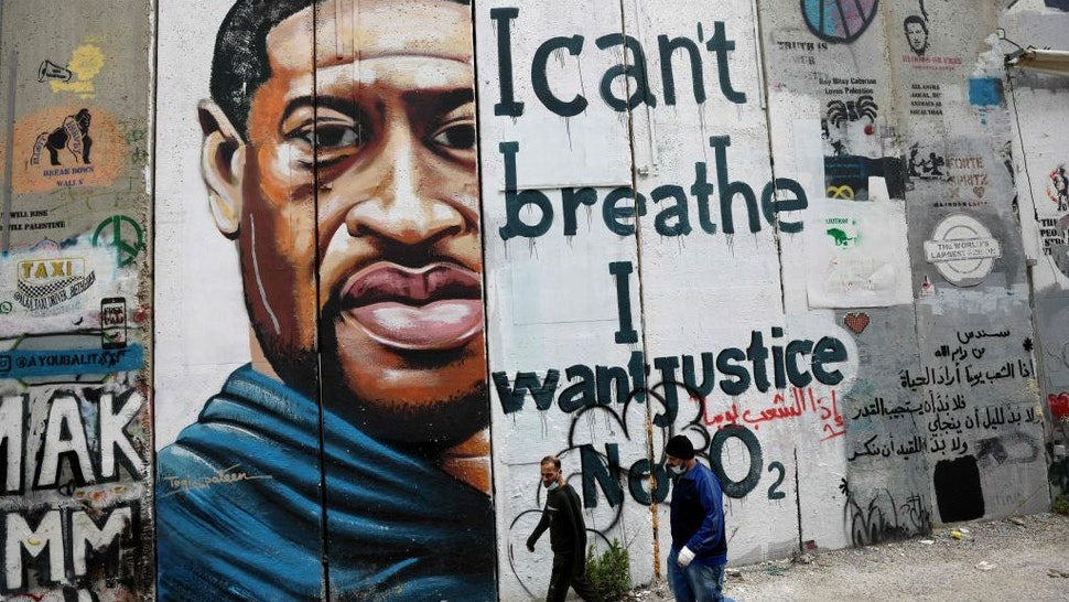 People walk past a mural showing the face of George Floyd, an unarmed handcuffed black man who died after a white policeman knelt on his neck during an arrest in the US, painted on a section of Israel's controversial separation barrier in the city of Bethlehem in the occupied West Bank on March 31, 2021. (Photo by Emmanuel DUNAND / AFP) (Photo by EMMANUEL DUNAND/AFP via Getty Images)