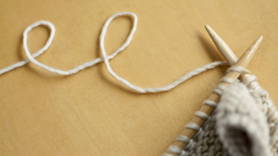 line of wool string connected to knitting project - stock photo