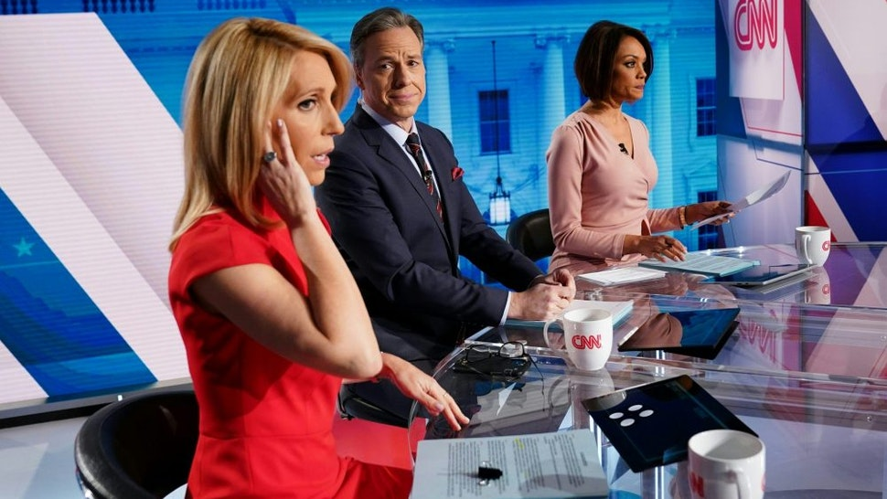 CNN news anchor Jake Tapper (C), flanked by Univision's news anchor Ilia Calderón (R), watches as co-anchor Dana Bash adjusts her ear piece before the start of the 11th Democratic Party 2020 presidential debate with former Vice-President Joe Biden and Vermont Senator Bernie Sanders in a CNN Washington Bureau studio in Washington, DC on March 15, 2020.