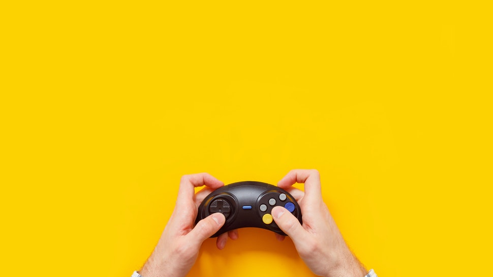 Cropped Hand Of Man Holding Joystick Over Yellow Background - stock photo