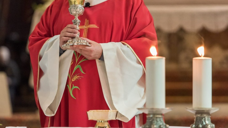 Midsection Of Priest Praying At Table In Church