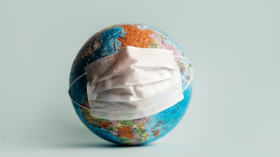 Globe made of jigsaw puzzles with a protective medical mask - stock photo