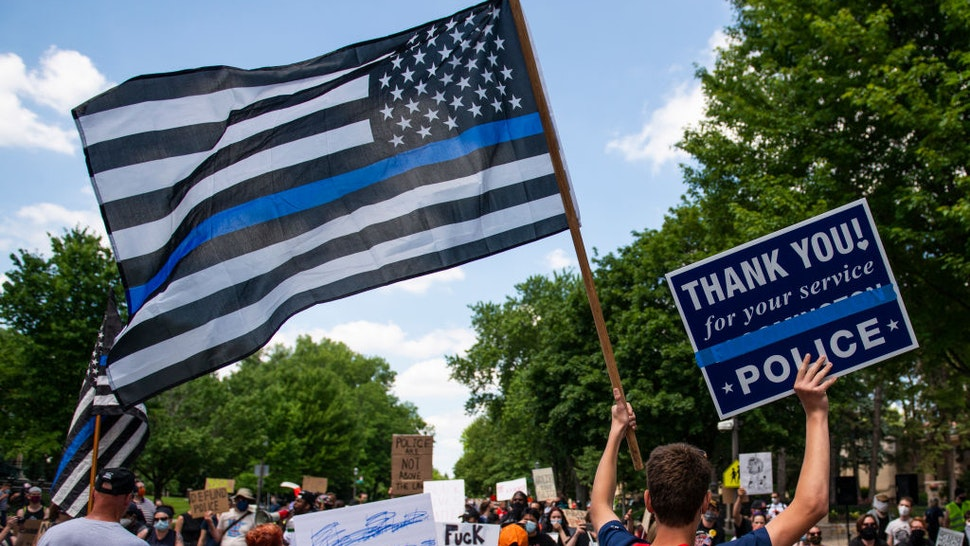 """ST PAUL, MN - JUNE 27: A demonstrator holds a """"Thin Blue Line"""" flag and a sign in support of police during a protest outside the Governors Mansion on June 27, 2020 in St Paul, Minnesota. A group called """"Bikers for 45"""" advocating a pro-police stance arranged the protest and were met with counter-protesters calling for measures to defund police."""