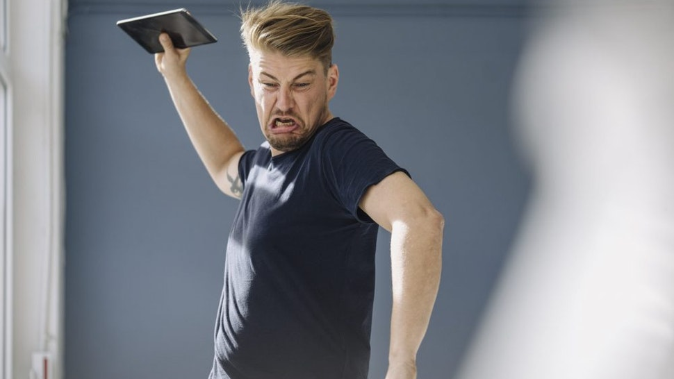 Angry man throwing tablet away